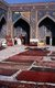 The Registan contains three madrasahs (schools), the Ulugh Beg Madrasah (1417–1420), Tilya-Kori Madrasah (1646–1660) and the Sher-Dor Madrasah (1619–1636).<br/><br/>  The Tilya-Kori Madrasah was built in the mid-17th century by the Shaybanid Amir Yalangtush. The name Tilya-Kori means 'gilded' or 'gold-covered', and the entire building is lavishly decorated with elaborate geometrical arabesques and sura from the Qur'an both outside and especially within. A magnificent turquoise dome rises over the left (western) side of the building, decorated inside with gilded Qur'anic inscriptions and delicate muqarnas hanging 'stalactite' decorations. The interior of the madrasah comprises rooms for students with accompanying vestibules surrounding three-sides of a square courtyard, while a domed mosque occupies the fourth.<br/><br/>  The dome rises in four stages. A rectangular plinth forms the primary prayer hall and rises above the madrasa walls. Next, two terraced octagonal tiers rise to support a high cylindrical drum. The dome's monochrome blue color contrasts pleasingly with the drum's polychrome decoration formed by bands of Arabic calligraphy taken from the Qur'an.
